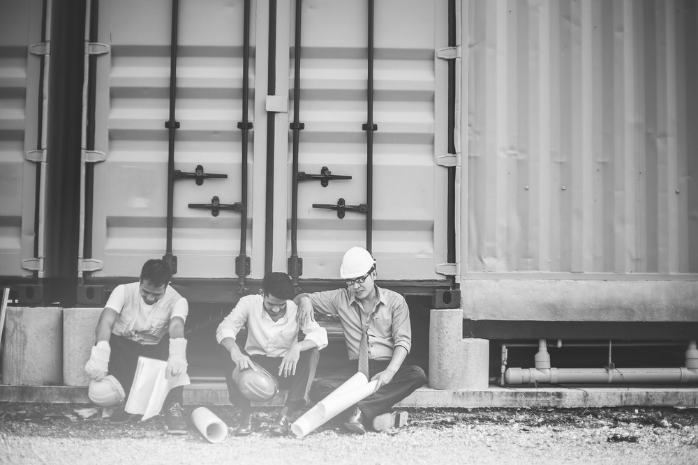 three construction workers sitting beside a building and resting after work