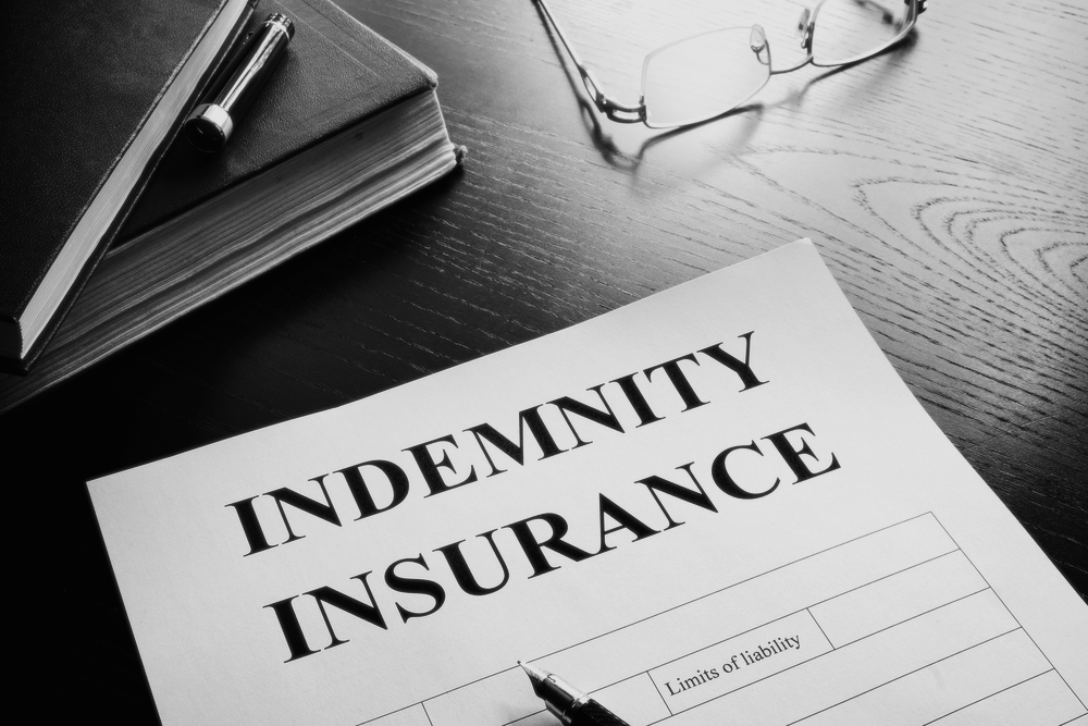 indemnity insurance form on wooden desk with books and glasses