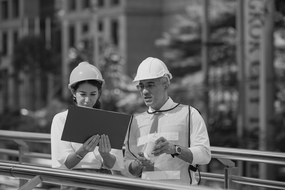 female contractor with hardhat reviewing design plans with male contractor with hardhat