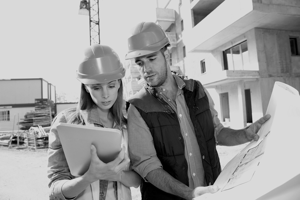 female contractor holding notepad with male contractor holding jobsite sketch outside