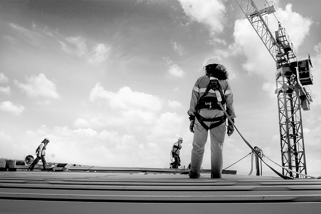 Construction working on a harness on top of a roof