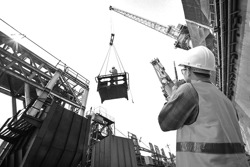 Construction worker lifting crane and using walkie talkie.