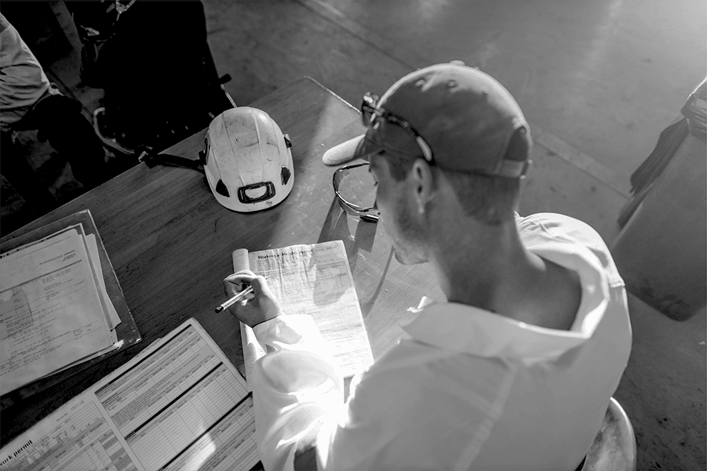 Construction worker filling out paperwork at a desk