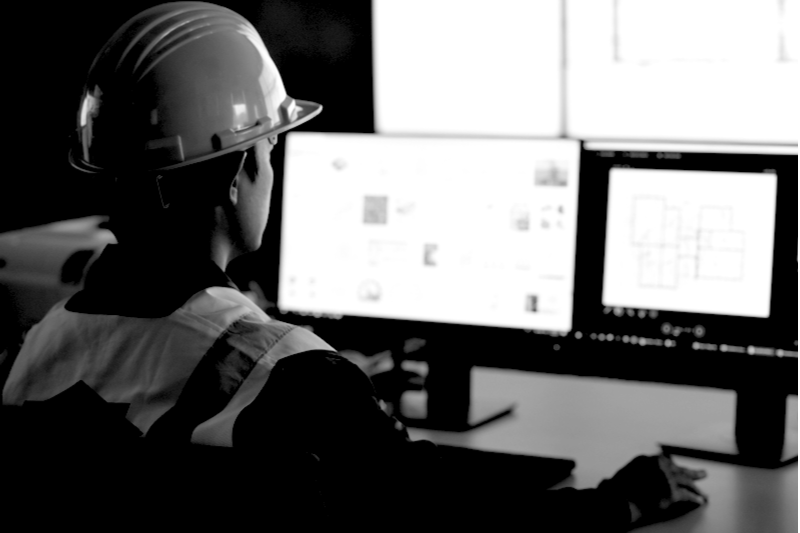 Construction worker at desktop working on spreadsheets in an office