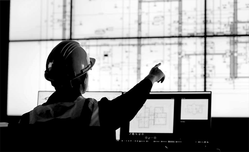 Construction contractor in a cyber room with blueprints on screen
