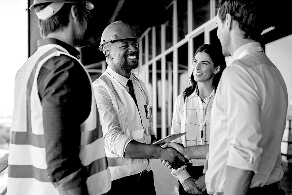 Contractor and insurance broker shaking hands on a construction site