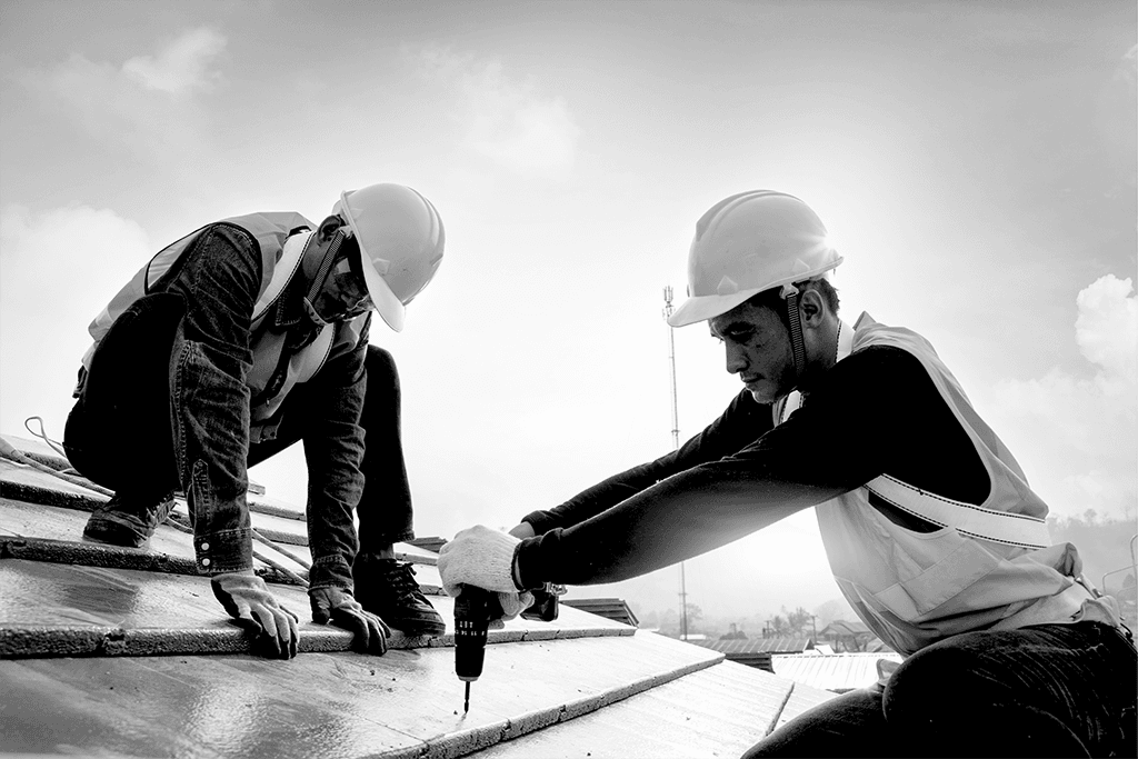 Two construction workers with a drill on a roof