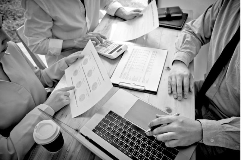 contractors around laptops, graphs and calculators