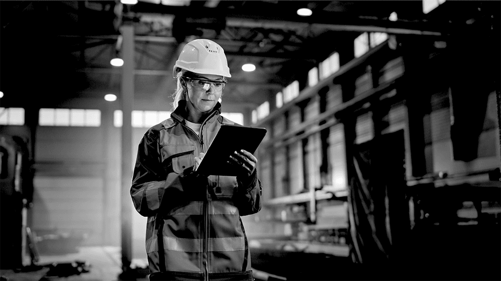 Woman in construction working on her clipboard in a factory with hardhat