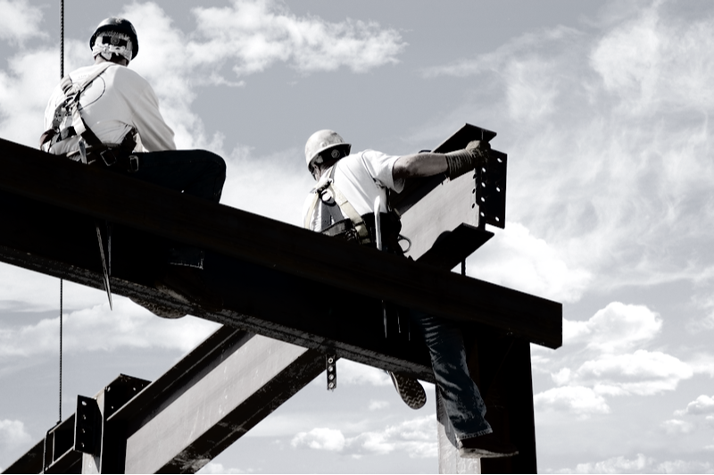 Construction workers on i-beam installing framework for a building without safety gear