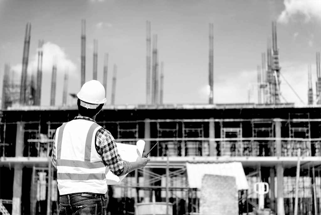 Engineer on construction site holding blueprint in his hand