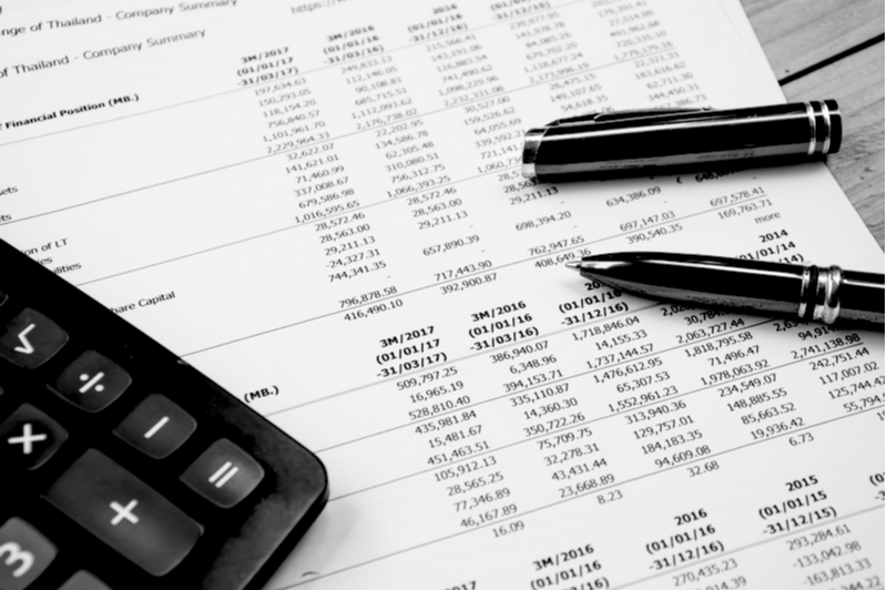 Calculator resting on financial statements with pen