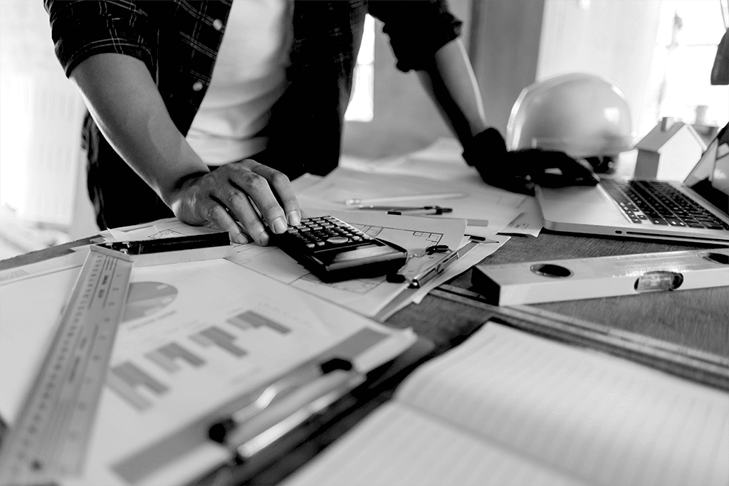 architect man working with laptop and blueprints, architectural plan with calculator in loft office,Building Design,Home or house town planning, engineering tool for sketching a construction project