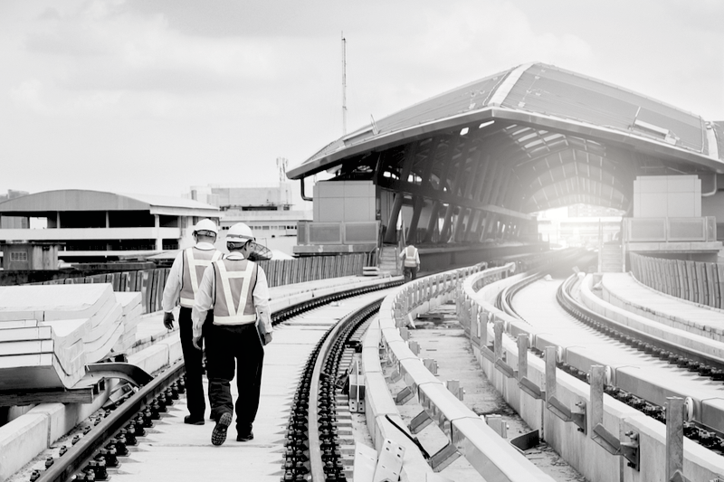 Inspector (Engineer) checking railway construction work on skytrain viaduct. Which railway consist of rail track and conductor rail or third rail.