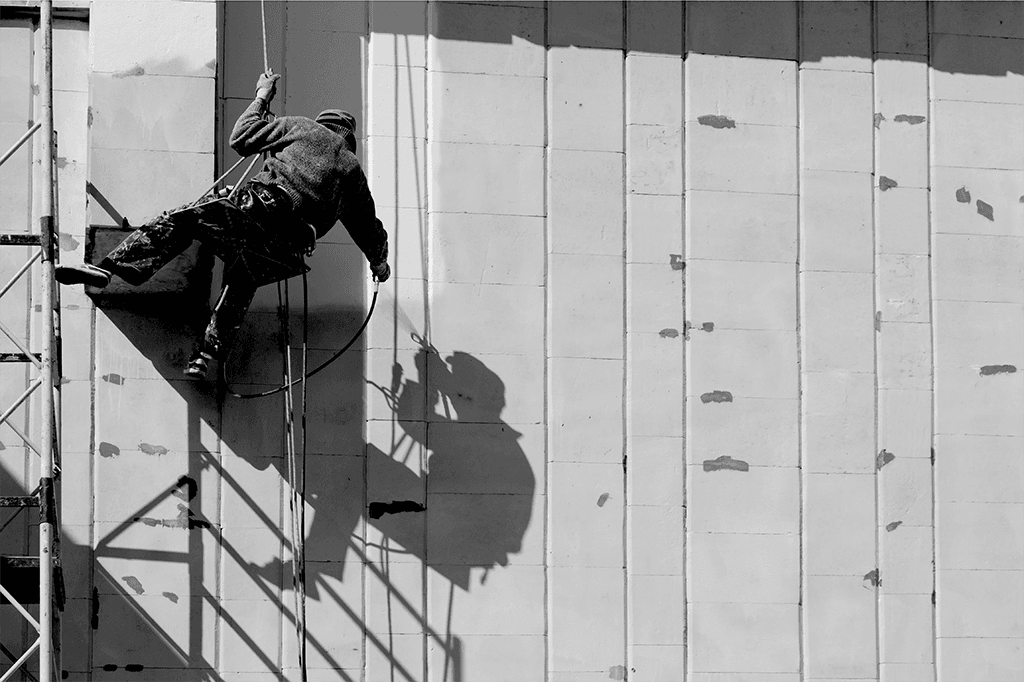 Construction worker perilously handing from the side of a building