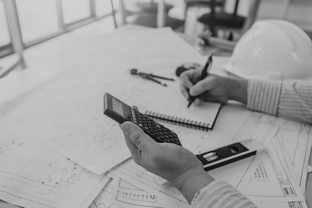 worker with calculator and notepad at a desk with construction documents