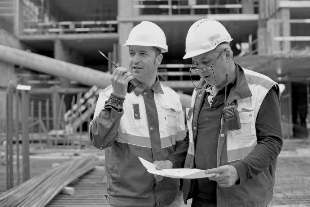 two senior construction workers with hardhats reviewing documents at construction site