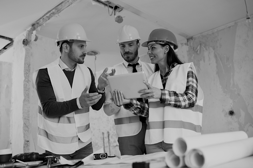 three construction workers with hard hats and uniforms reviewing plans together in work building
