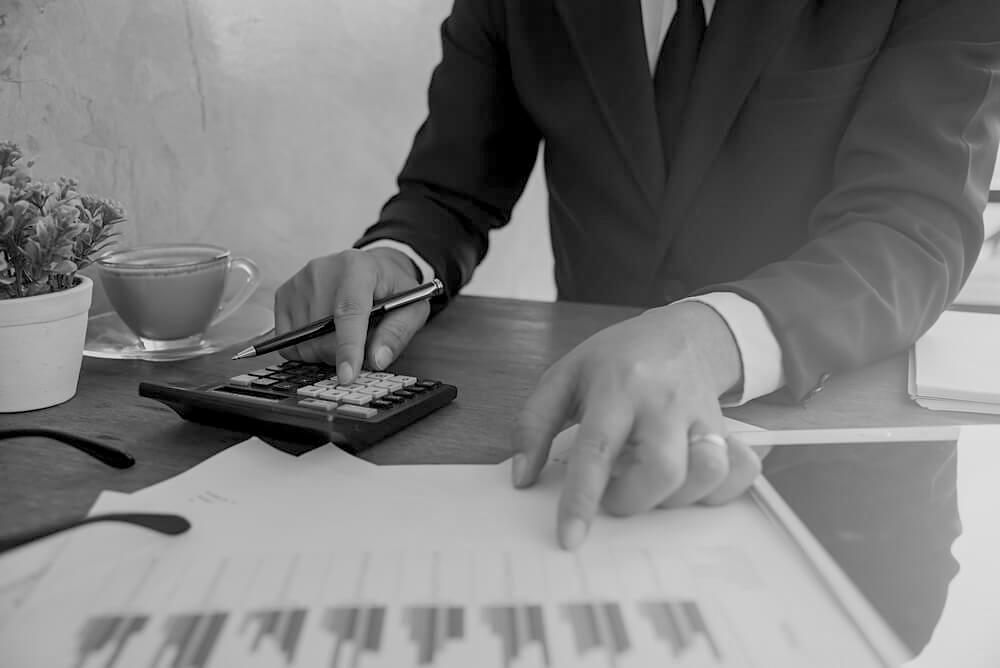 businessman in black suit at desk using calculator and pen while pointing at a printed data sheet
